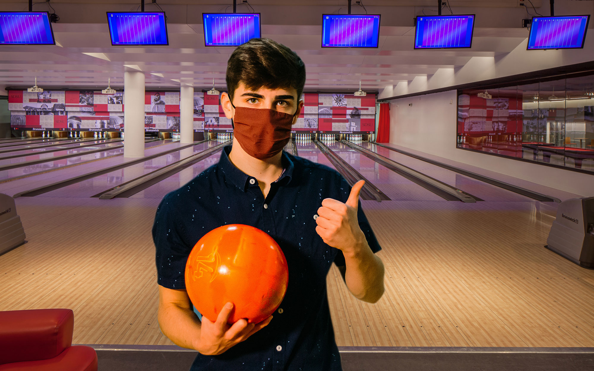 Man wearing a face mask, holding a bowling ball in Aztec Lanes