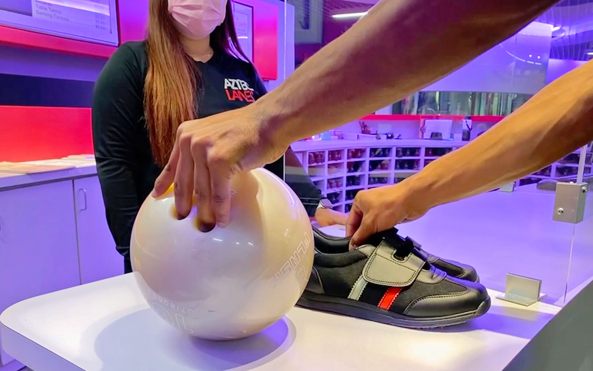 Picking up a bowling ball and shoes from front desk