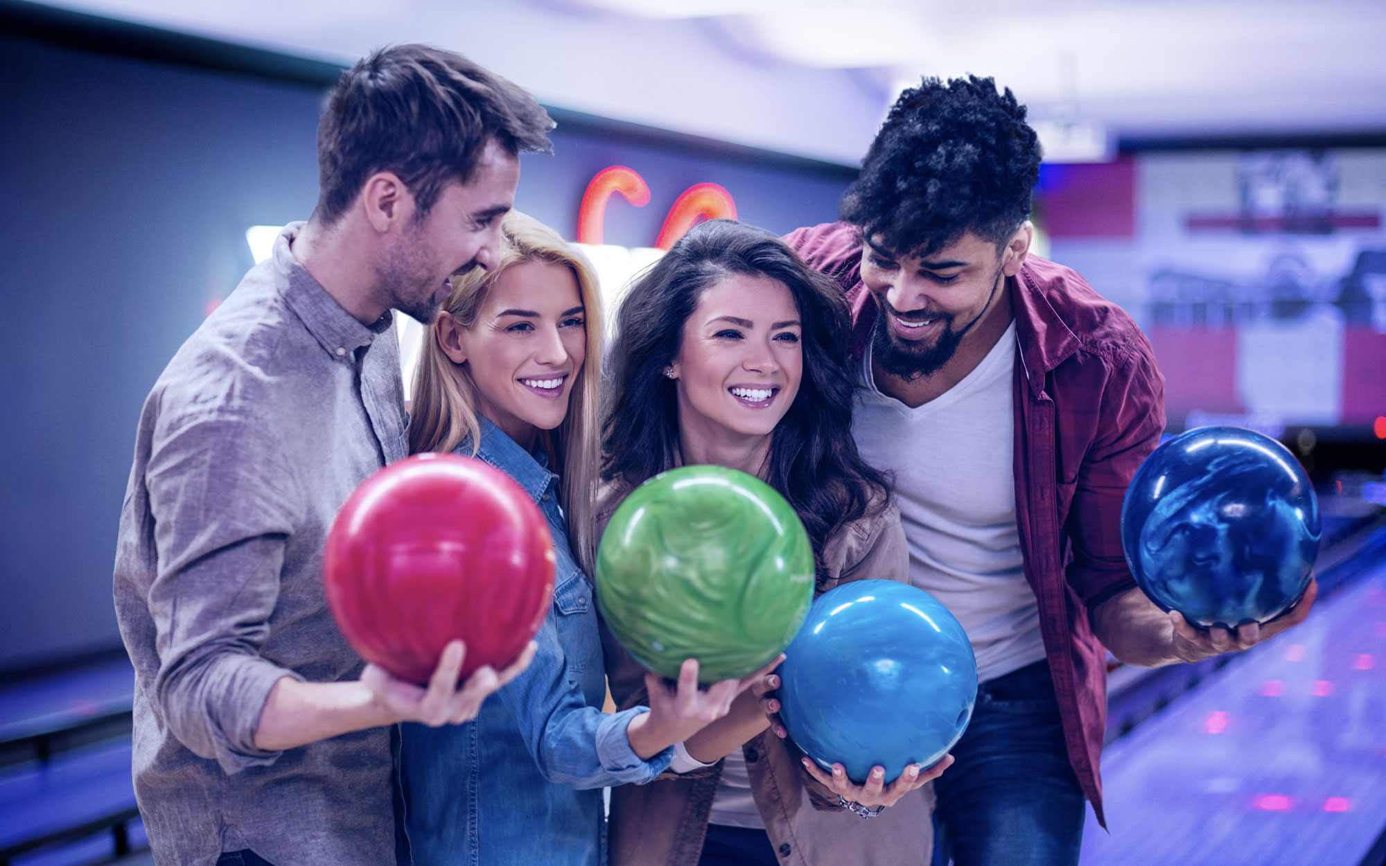 Four smiling friends holding bowling balls