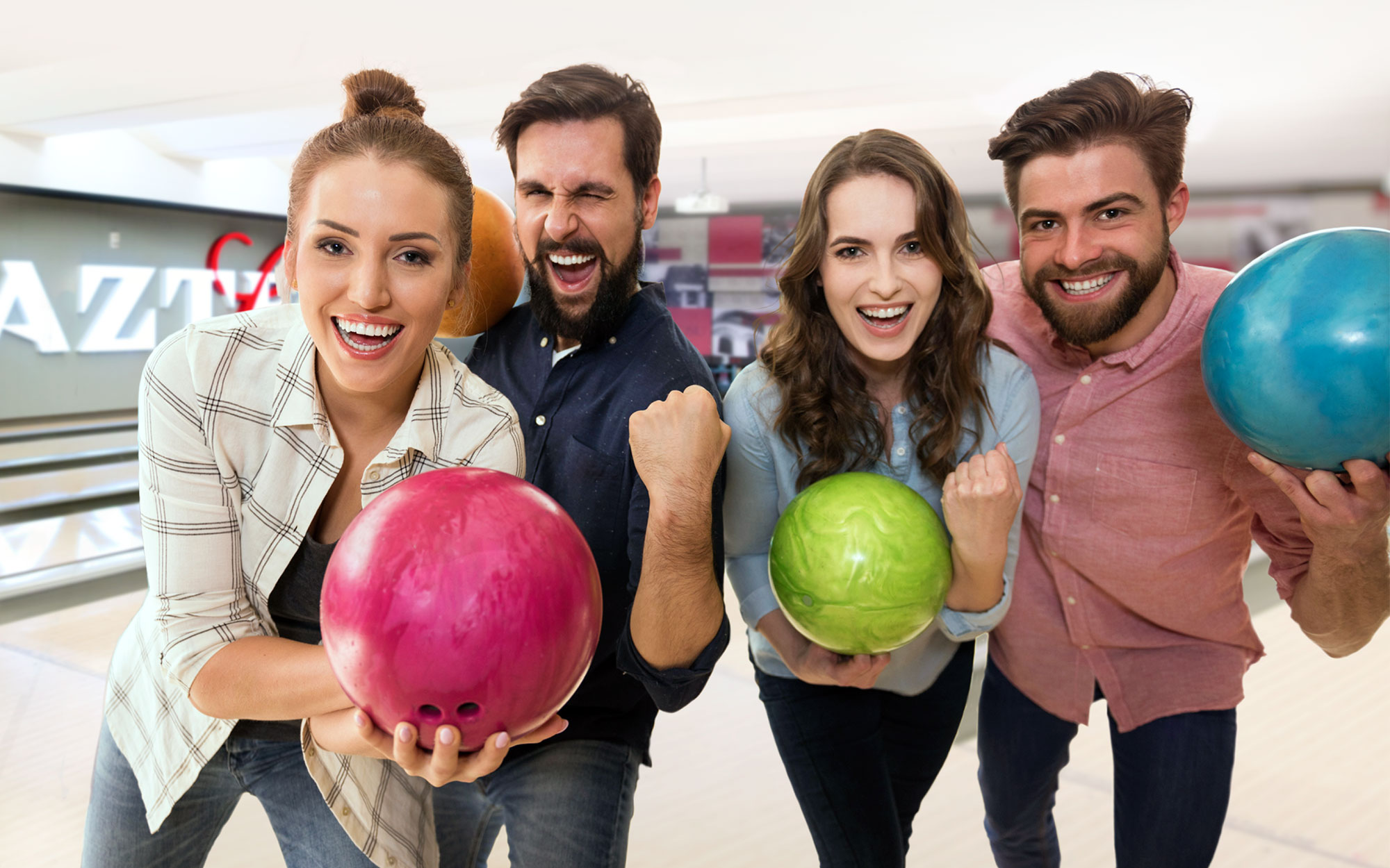 Four smiling friends holding bowling balls at an private event at Aztec Lanes