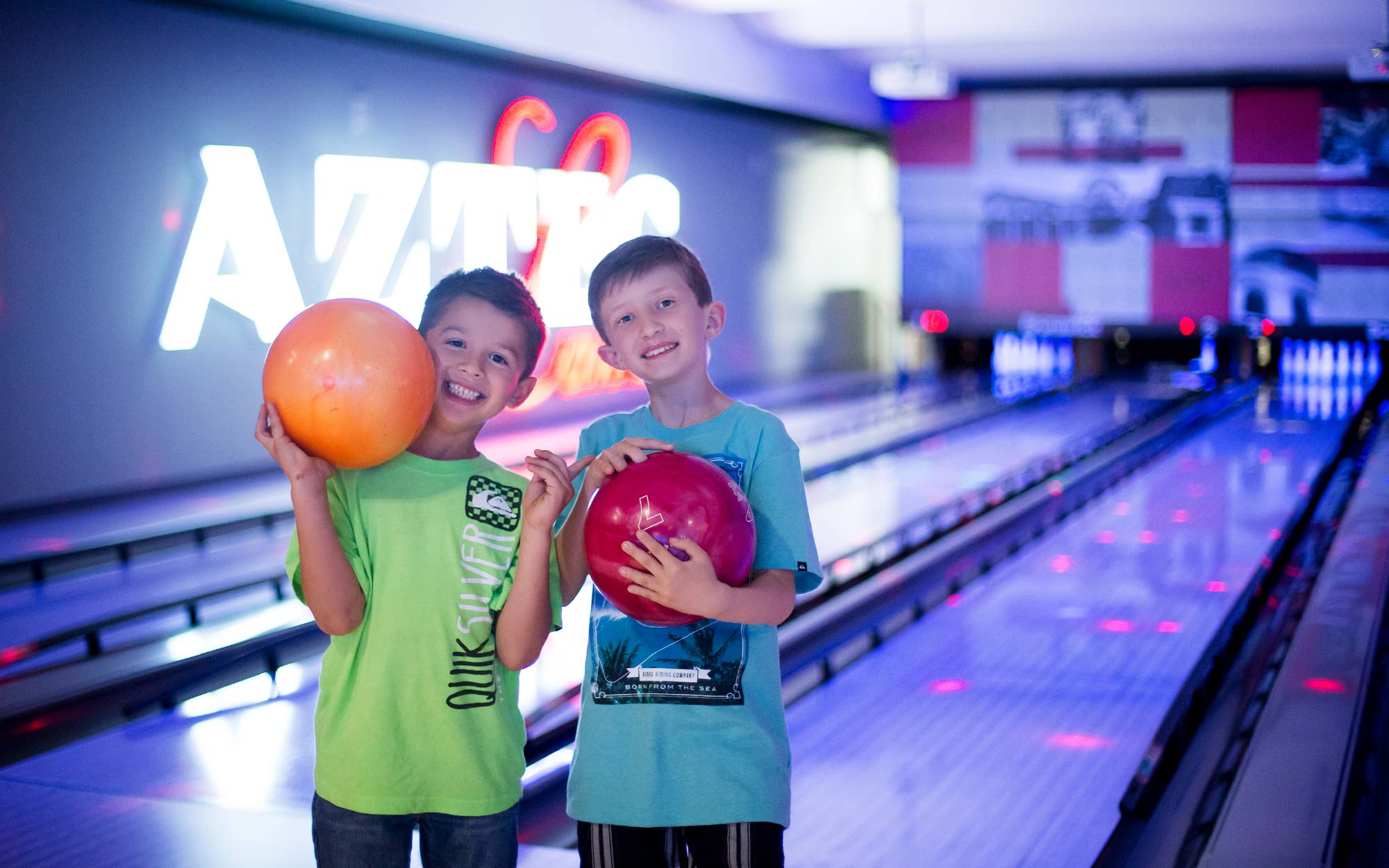 Two smiling boys holding bowling balls at Aztec Lanes