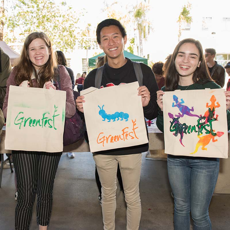 Three students showing off self-painted reusable bags