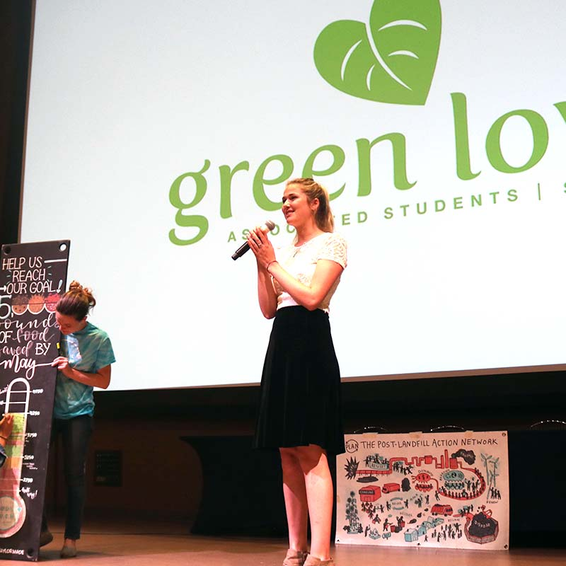 Female speaker on stage at a GreenLunch Bag event