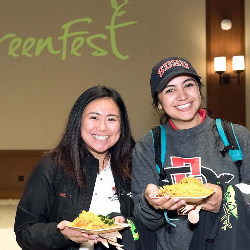 Two female students with plates of food at a GreenFest Event