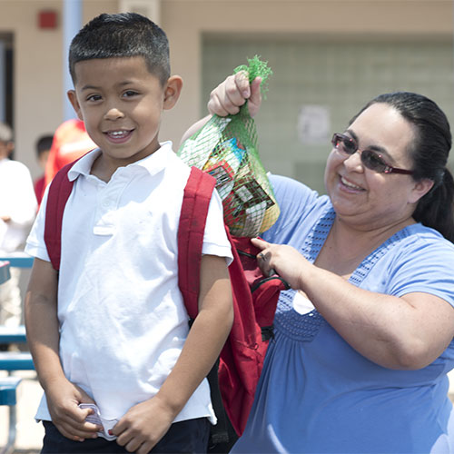 Woman outting bag of food in boy's backpack