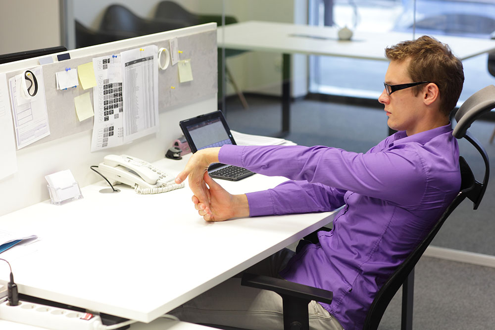 Man at desk doing hands stretching exercises?2020-10-22